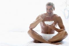 Medio Volwassen Mens die een Kom Graangewas eet stock foto's