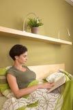 Medio-volwassen mooie vrouwenlezing in slaapkamer Royalty-vrije Stock Foto