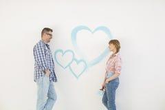 Medio-volwassen paar die elkaar met geschilderd hart op muur bekijken Royalty-vrije Stock Afbeeldingen