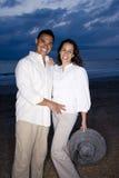 Medio-volwassen Spaans paar dat op strand bij dageraad glimlacht stock foto's