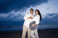 Medio-volwassen Spaans paar dat op strand bij dageraad glimlacht royalty-vrije stock afbeelding