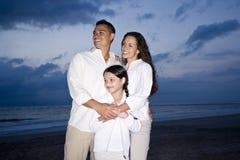 Medio-volwassen Spaanse familie die op strand bij dageraad glimlacht stock afbeeldingen