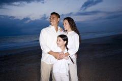 Medio-volwassen Spaanse familie die op strand bij dageraad glimlacht Royalty-vrije Stock Afbeeldingen