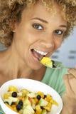 Medio Volwassen Vrouw die Verse Fruitsalade eet stock afbeelding