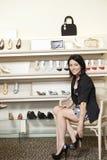 Medio volwassen vrouwelijke klant die op hielen in schoenopslag proberen Stock Fotografie