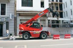 MEDIOLAN, ITALY-MAY 25, 2015: Parkujący czerwony budowa żuraw na placu budowy Zdjęcie Stock