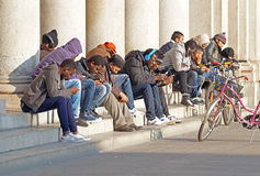 MEDIOLAN, WŁOCHY - 25 2015 Grudzień: Ludzie use telefonów komórkowych podczas gdy siedzący w kwadracie Zdjęcia Stock