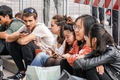 Mediolan, Włochy 04 Marzec 2018: młodzi ludzie siedzi w miasto kwadracie komunikują używać ich smartphone Zdjęcie Royalty Free