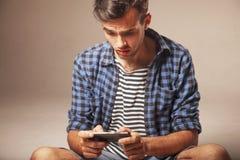 Medios apego social hombre joven que sostiene un psycholo del smartphone Imagen de archivo
