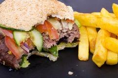 Medios cheeseburger y fritadas comidos Fotos de archivo libres de regalías