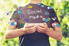 Medios concepto social con el hombre joven que sostiene su smartphone afuera Fotos de archivo