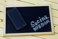 Medios concepto social con los MEDIOS SOCIALES del smartphone y de la palabra escritos en la pizarra Imagen de archivo libre de regalías