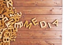 Medios de la palabra hechos con las letras de madera Imagenes de archivo