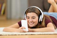 Medios de observación adolescentes felices en un smartphone en casa Imagen de archivo