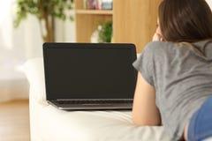 Medios de observación de la muchacha en un ordenador portátil que muestra la pantalla Fotografía de archivo libre de regalías
