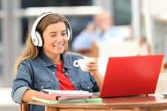 Medios de observación del estudiante relajado en línea en una cafetería Fotos de archivo libres de regalías