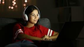 Medios de observación de la muchacha en un ordenador portátil en la noche en casa