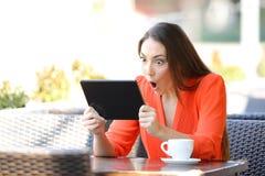 Medios de observaci?n y que escuchan de la mujer chocada en la tableta foto de archivo libre de regalías