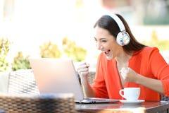 Medios de observaci?n y que escuchan de la mujer emocionada en el ordenador port?til imagen de archivo libre de regalías