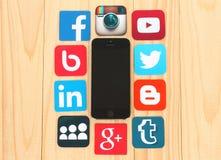 Medios iconos sociales famosos alrededor del iPhone en fondo de madera Imagen de archivo libre de regalías