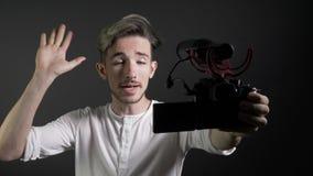Medios influencer social popular que sostiene la cámara y que registra un vídeo en un estudio profesional con el fondo oscuro - almacen de video