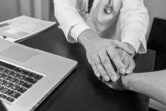 Medique as mãos do ` s que guardam a mão paciente do ` s para o incentivo Imagem de Stock