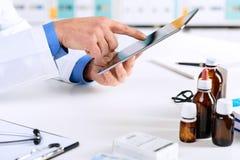 Medique as mãos do ` s que trabalham em uma tabuleta digital em seu escritório imagem de stock