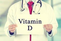Medique as mãos que guardam o sinal branco do cartão com mensagem de texto da vitamina D Foto de Stock