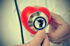 Medique auscultating um coração com um estetoscópio, com um EFF retro Imagem de Stock Royalty Free