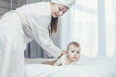Medique desafios e deleites uma criança pequena em uma sala Imagem de Stock