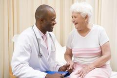 Medique a doação do controle à mulher no quarto do exame Imagens de Stock