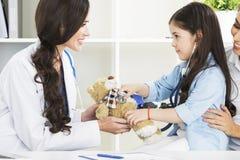 Medique e seu paciente pequeno com urso de peluche Fotografia de Stock Royalty Free