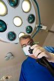 Medique em uma veste azul e em olhares da máscara no dispositivo foto de stock