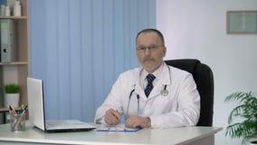 Medique a escrita no informe médico dos pacientes, olhando na câmera, serviços da clínica video estoque
