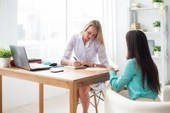 Medique a fala ao paciente no escritório, tomando notas Fotos de Stock Royalty Free