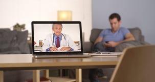 Medique a fala ao paciente que texting em seu smartphone imagens de stock
