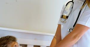 Medique a fala com o paciente envelhecido sênior na cama 4k video estoque