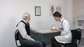 Medique a fala a seu paciente superior masculino e a escrita de algo vídeos de arquivo