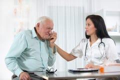 Medique a fala a seu paciente superior masculino no escritório Imagens de Stock