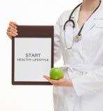 Medique guardar uma prancheta e uma maçã verde Fotografia de Stock