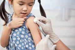 Medique a injeção da vacinação no braço da menina asiática da criança pequena fotografia de stock royalty free