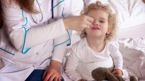 Medique a mão que dá a dose da colher do xarope bebendo líquido da medicina à criança filme