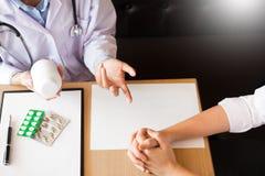 Medique a mão que guarda a tabuleta da droga e explique-a ao paciente em ho fotografia de stock royalty free