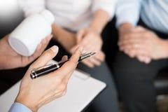 Medique a mão que guarda a tabuleta da droga e explique-a ao paciente em ho fotografia de stock