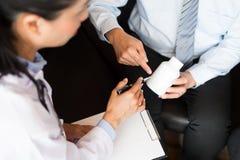 Medique a mão que guarda a tabuleta da droga e explique-a ao paciente em ho imagem de stock