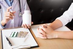 Medique a mão que guarda a tabuleta da droga e explique-a ao paciente em ho fotos de stock