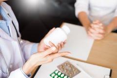 Medique a mão que guarda a tabuleta da droga e explique-a ao paciente em ho fotos de stock royalty free