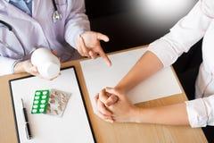 Medique a mão que guarda a tabuleta da droga e explique-a ao paciente na sala de hospital foto de stock royalty free