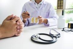 Medique a mão que guarda a tabuleta da droga e explique-a ao paciente na sala de hospital fotografia de stock