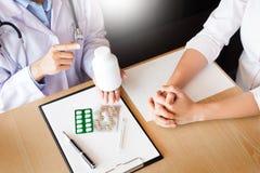 Medique a m?o que guarda a tabuleta da droga e explique-a ao paciente na sala de hospital imagens de stock